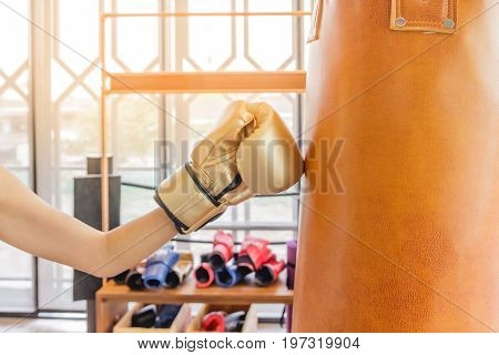 Beautiful Kickboxing woman training punching bag in fitness studio fierce strength fit body kickboxer series. Sexy fighter girl punching actively.