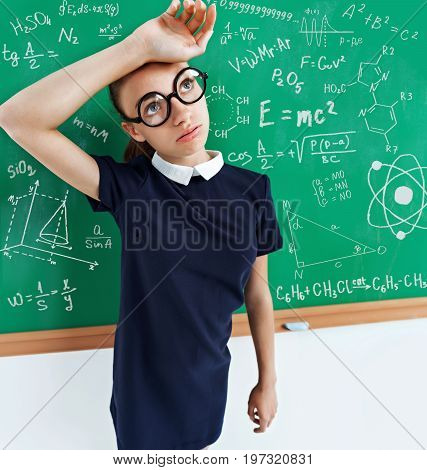 Tired student solved all the examples on the blackboard. Photo of a smart student in uniform education concept.