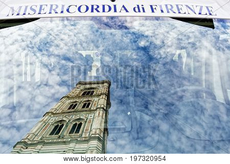 Florence Italy - October 17 2016: Giotto Bell Tower reflected in window of Servizi Sociali Misericordia di Firenze car Florence Tuscany Italy