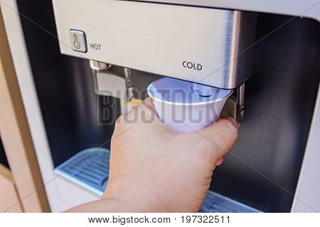 Drinking water using a paper cup for drinking water is a proper way to drink hygiene water and beverages. at water cooler water dispenser