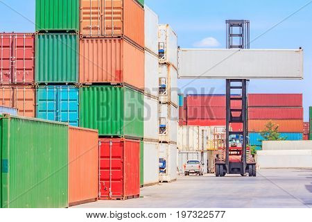 Forklift truck lifting cargo container in shipping yard or dock yard against blue sky cloudy with cargo container stack in background for transportation import Export and logistic industrial concept
