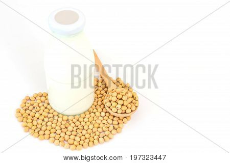 soy milk in glass bottle with soy beans in spoon isolated on a white background Closed up with copy space and text.