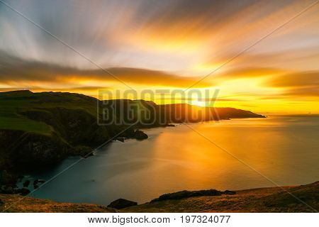 golden long exposure sunset over the sea and sea cliffs