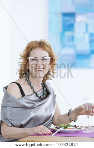 Older woman sitting at the table and smiling
