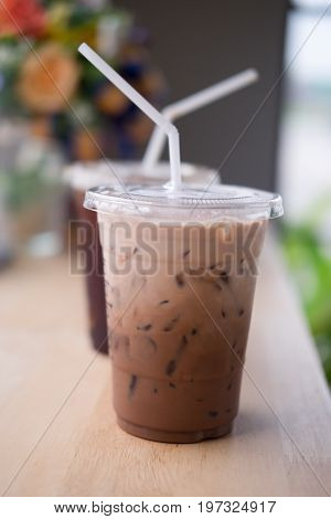 Iced chocolate in takeaway cup on wooden table