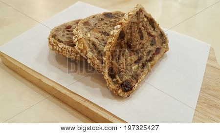 whole wheat fruit bread with raisin nut and grain on wooden chopping block / whole wheat fruit bread