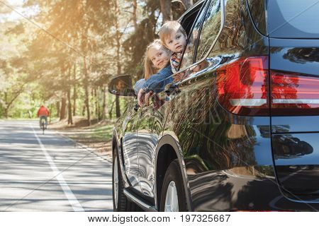 Travel by car family ride together brother and sister lean out of the window