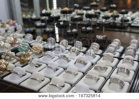luxury Rings with gems on display in showcase of jewelry store , selective focus