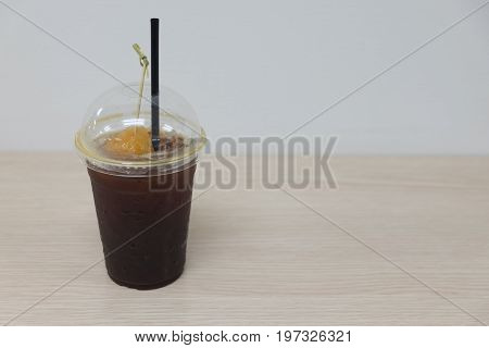 Black coffee with slice peach (Fusion drink) on wood table