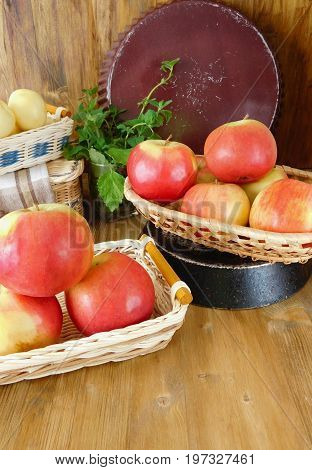 Apples in wicker baskets on a wooden table