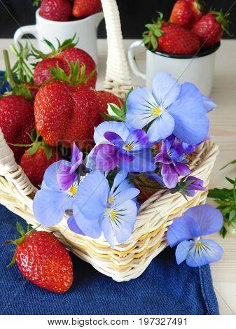 Fresh ripe strawberries and pansies in a wicker basket