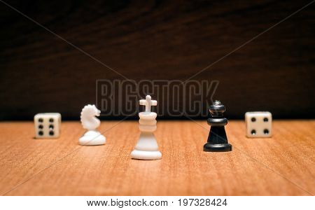 Chess king horse and queen as well as dice on a dark wooden background items for popular board games