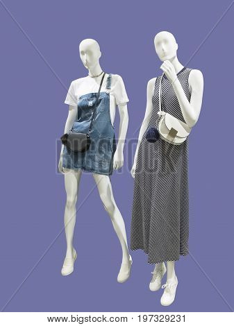 Two full-length female mannequins dressed in fashionable clothes isolated. No brand names or copyright objects.