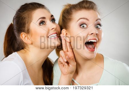 Young woman telling her friend some secrets two women talking gossiping. Excited emotional girl whispering to ear