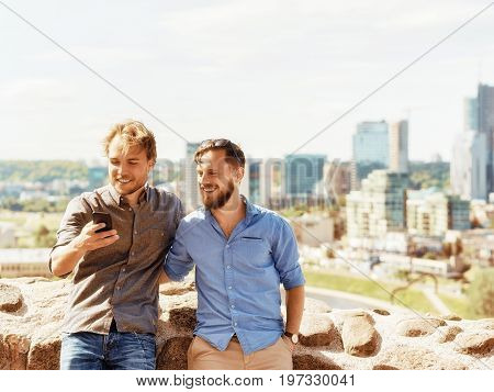 Smiling Young Caucasian Buddies Having Fun Looking Pictures At Mobile