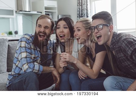 Friends having party together indoors singing karaoke