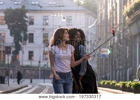 Two attractive girls making selfie in a beautiful city. One girl is african american.