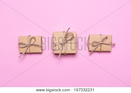 A three gifts wrapped in kraft paper on a pink background. View from above, flat lay design