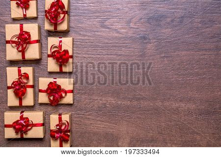 gifts wrapped in kraft paper and red ribbon and bow on a wooden background. View from above, flat lay design.