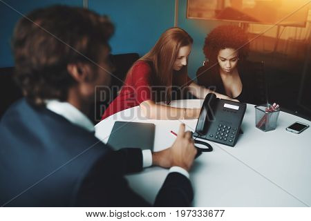 Scene in meeting room: two businesswomen (caucasian and Brazilian) and one man employer are sitting at oval table and waiting their colleagues to start business meeting on sunny day in office interior