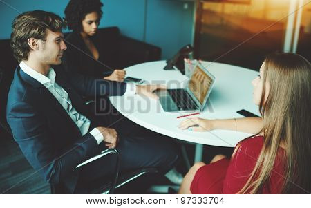 Handsome adult businessman listening attentively of his female colleague in red dress while sitting in meeting room three together with one more co-worker during work team meeting with laptop at table