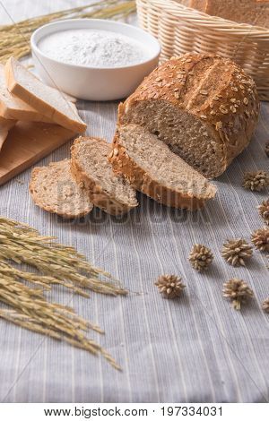 Freshly baked traditional wheat bread and wheat and oat on white pattern linen tablecloth soft focus