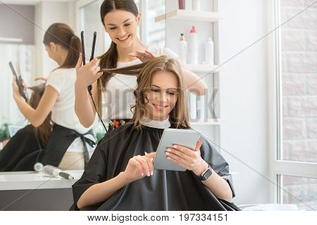 Young female sitting in hair salon hairdo styling using digital device