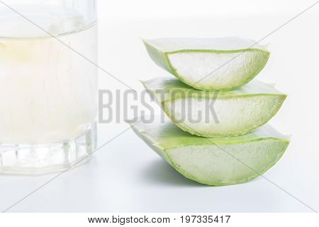 a stack of aloe Vera leaf stems with a glass of gell