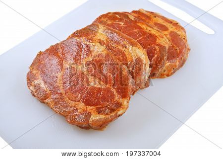 Meat Pork neck in marinade and on a chopping boardon on a white background