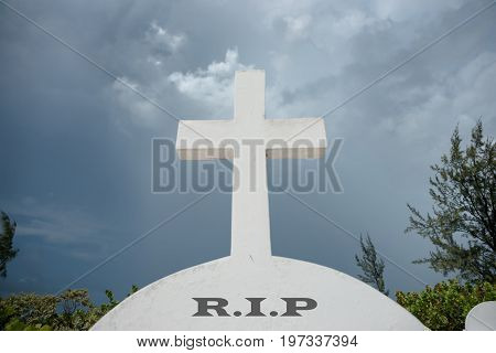 White cross above letters RIP on headstone under foreboding dark cloudy sky.