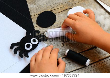 Felt Halloween spider ornament, thread, needle, paper templates, filler, white and black felt sheets on a vintage wooden table. Child takes a thread in his hand. Easy hand sewing projects for children