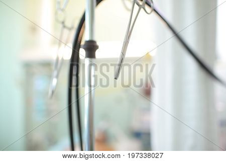 Tube and forceps hanging on the tripod in the ward.