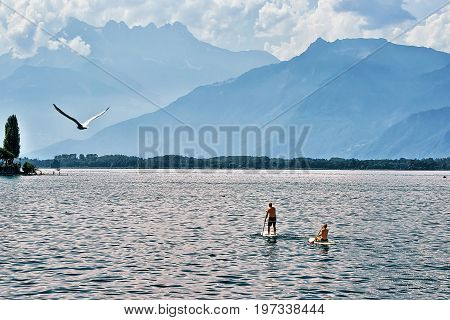 Couple standing on Standup paddle surfing board on Geneva Lake in Montreux Vaud canton Switzerland