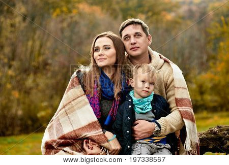 Portrait of happy cute family basking with plaid in park