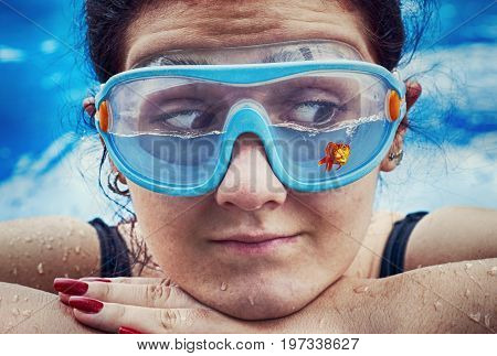 Young woman wearing swimming glasses half filled with water and a fish .