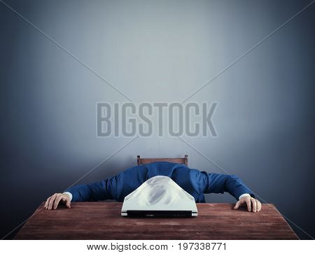 Business man with his head stucked into a closed laptop. Overworked concept.