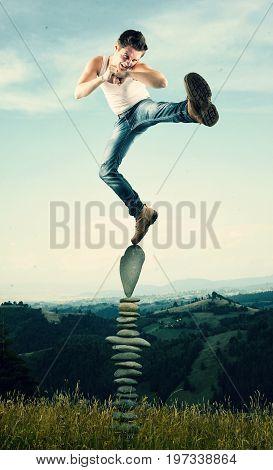 Man kicks and standing in balance on arranged rocks.