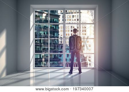 Back view of young businessman looking out of window in minimalistic unfurnished concrete interior with city view. Research concept. 3D Rendering