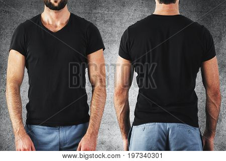 Shirt design and people concept. Close up of guy in blank black t-shirt front and rear view. Clean empty mock up template for your design. Concrete background