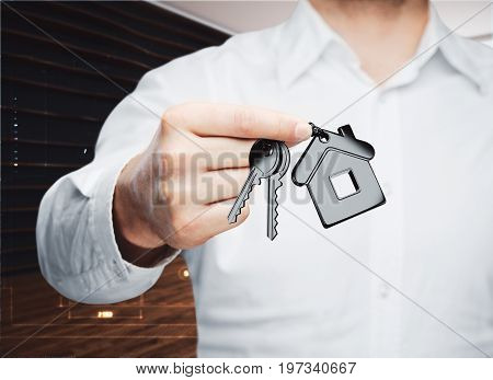 Businessman holding key with house keychain in modern interior. Mortgage concept. 3D Rendering