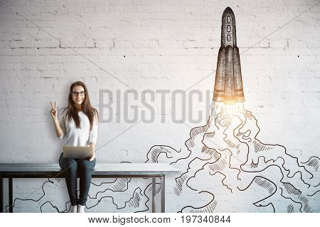 Happy young european woman sitting on table with laptop and showing peace sign on white brick background with launching rocket sketch. Startup concept