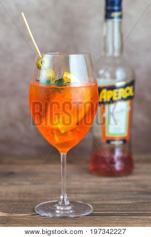 SUMY UKRAINE- JULY 27 2017: Glass of Aperol Spritz cocktail with bottle of Aperol on the wooden background. Aperol is famous Italian aperitif.