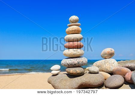Colored stones balance on a background of blue sky and sea. Concept of balance and harmony