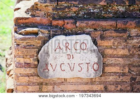 Arco Di Augusto Sign On Brick Wall In Rome