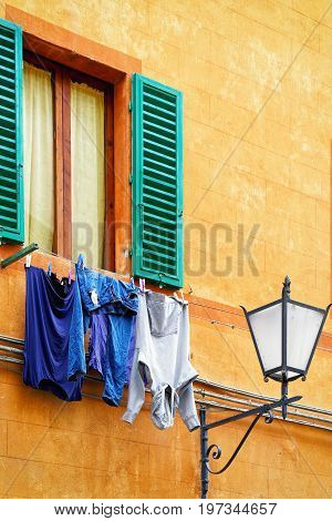 Traditional House With Clothesline And Street Lantern In Siena