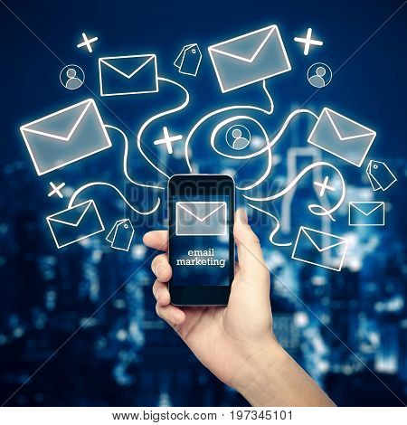 Hand holding cellphone with abstract email network hologram on nigth city background. E-mail marketing concept