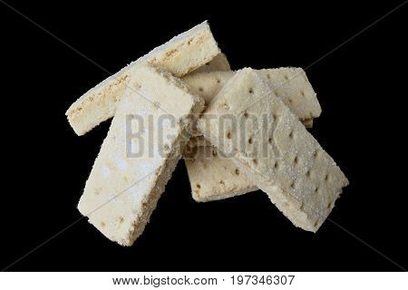 Pilers of shortbread biscuits isolated on a black background and centred in the image. The biscuits are sugar coated and covered in crumbs.