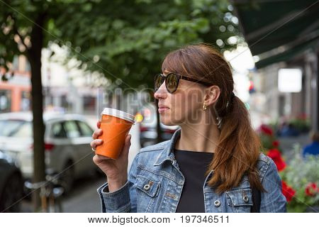 woman enjoying her morning on go coffee on her way to work