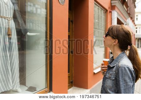 Window shopping concept. Young woman looking in a shop window.