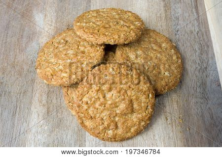 A pile of oatmeal biscuits on a wooden board. The biscuits are piled in the centre of the board and are piled on top of each other. A focus stacked image